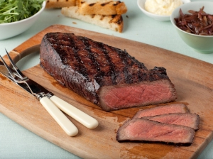 Sliced London Broil on a wooden cutting board alongside white handled cutlery